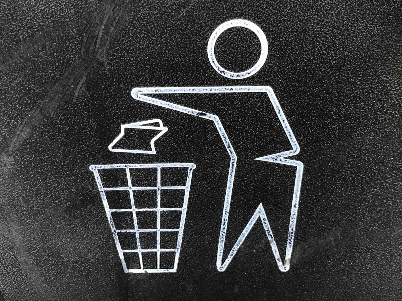 A silhouette cartoon figure throwing trash away.