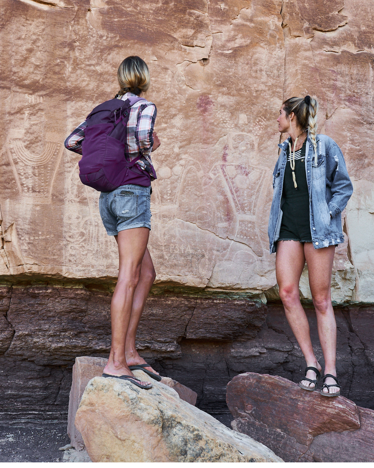 Two hikers looking at petroglyphs at Smithsonian Butte, Dinosaurland, Utah