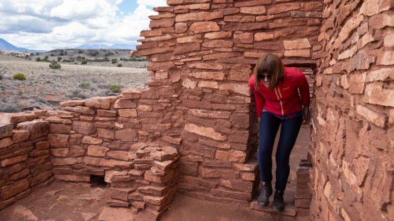 woman walking through ancient ruins