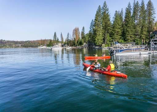 Family kayaking on Bass Lake in Madera County, California