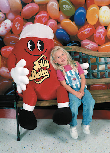 Girl and Jelly Belly character on bench