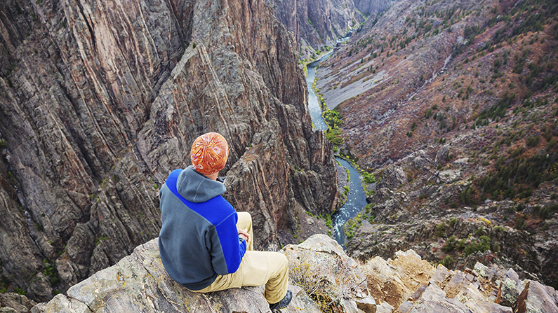 Hiker looking down at Black Canyon of Gunnison on the San Juan Skyway route