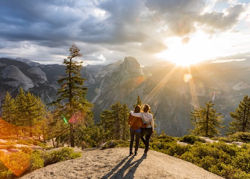 Two people watching sunrise at Glacier Point in Yosemite National Park