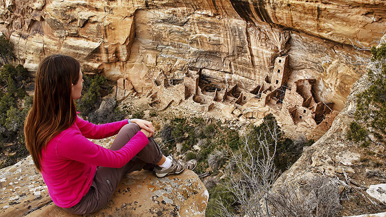 Woman looking down at cliff dwellings in Mesa Verde National Park